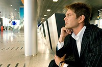 Businessman sitting at an airport lounge with his hand on his chin