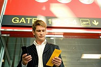 Low angle view of a businessman holding a boarding pass and using a mobile phone