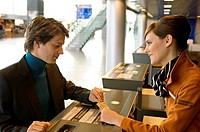 Businessman with a female check_in attendant at an airport check_in counter