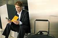 Businessman sitting at an airport and operating a mobile phone