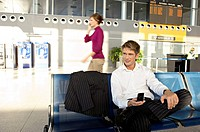 Businessman holding a mobile phone and sitting at an airport lounge