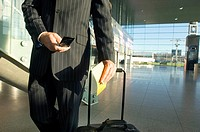 Mid section view of a businessman using a mobile phone at an airport