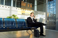Businessman using a laptop and talking on a mobile phone at an airport lounge