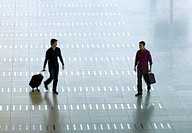 High angle view of a mid adult man and a young man walking at an airport lobby