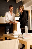 Young woman showing a Christmas present to a mid adult man