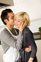 Side profile of a young man kissing a young woman in the kitchen (thumbnail)