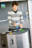 Mid adult man putting an empty bottle into a garbage bin