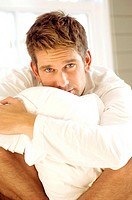 Portrait of a mid adult man hugging a pillow
