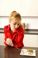 Young woman leaning against a kitchen counter and looking at a plate of rice