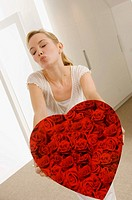 Young woman holding a heart shape gift and puckering her lips (thumbnail)