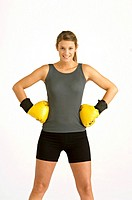 Portrait of a female boxer standing with arms akimbo and smiling