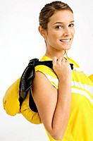 Portrait of a female boxer carrying boxing gloves on her shoulder and smiling
