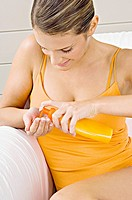 Close_up of a young woman squeezing moisturizer from a bottle