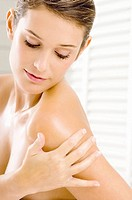 Close_up of a young woman applying moisturizer on her shoulder