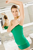 Portrait of a young woman applying deodorant on her underarm