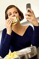 Close_up of a young woman eating a burger and looking at a mobile phone