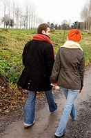 Rear view of a young couple walking on a dirt road
