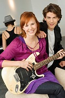 Portrait of a young woman playing a guitar with a teenage boy sitting beside her