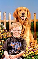 boy _ sitting in front of Golden Retriever