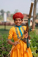 Portrait of boy playing musical instrument in traditional clothing, Jaipur, Rajasthan, India
