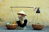 Hawker selling fruit at roadside, Hanoi, Vietnam