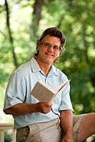 Smiling man reading book outdoors