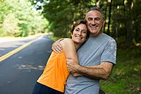 Jogging couple embracing at roadside