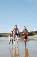 Man running with his two sons on beach