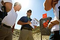 Instructor holding clipboard with target diagram at combat training