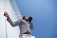 Man standing in front of a sail, looking through a spyglass, low angle view