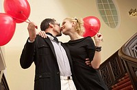 Couple with balloons embracing each other on a staircase