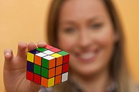 A woman with a colored cube in the hand
