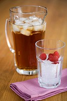 A can with ice tea and a crystal with ice cubes an a lot of raspberries