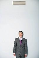Businessman standing under air conditioner
