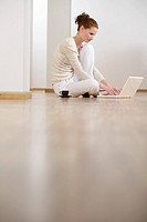 Young woman sitting on floor while using a laptop