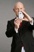 Businessman photographing with a mobile phone