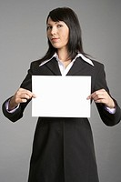 Businesswoman holding blank sign at camera