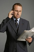 Businessman phoning with a mobile phone while reading a newspaper