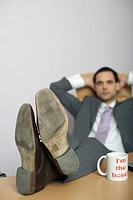 Businessman with feet on desk in office, coffee mug in foreground