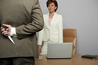 Businessman holding scissors behind back, facing businesswoman in office