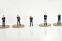 Businessman figurine between other ones standing on coins