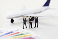 Three businessmen figurines between toy plane and banknotes