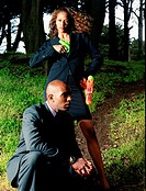 African American businesspeople outdoors with water guns.