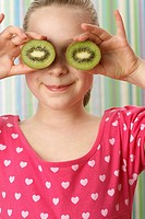 Girl holding kiwis to her eyes