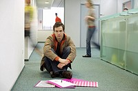 Young man sitting on a corridor floor