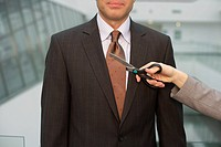 Person cutting businessman´s tie