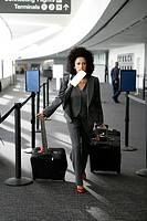 African American businesswoman pulling suitcases in airport.