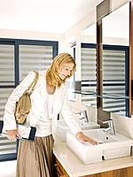 Woman viewing sink in design showroom