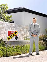 Real estate agent posing with sold home