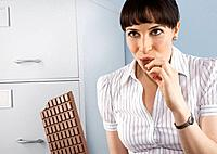 Businesswoman indulging in chocolate bar